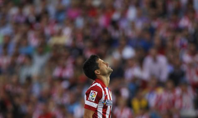 Atletico's Diego pauses,  during a Spanish La Liga soccer match between Atletico Madrid and Malaga at the Vicente Calderon stadium in Madrid, Spain, Sunday May 11, 2014. (AP Photo/Gabriel Pecot)