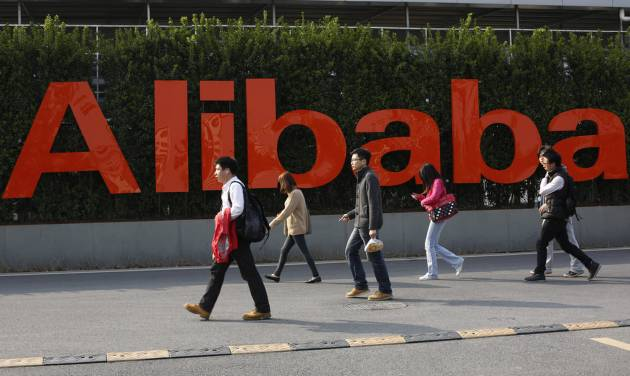 FILE - In this March 17, 2014 file photo, people walk past a company logo at the headquarters of Alibaba Group in Hangzhou, in eastern China's Zhejiang province. Alibaba is pulling back the curtain a little bit more Monday, June 16, 2014, providing more information about its partnership structure and financials ahead of its planned initial public offering. (AP Photo)  CHINA OUT