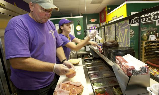 In this Friday, Aug. 3, 2012 photo, Walt and Nicole Mazie prepare food at their restaurant, The Big Easy, in Flagler Beach, Fla. Walt Mazie knows it was risky launching a business during hard times. Business was so dismal at first that on some Friday nights, Mazie says, he and his wife sat outside because there were no customers. They held on, though, and about six months ago, there was a turnaround. Mazie says business has increased about 65 percent over last year, thanks to positive publicity and an improved economy. (AP Photo/John Raoux)