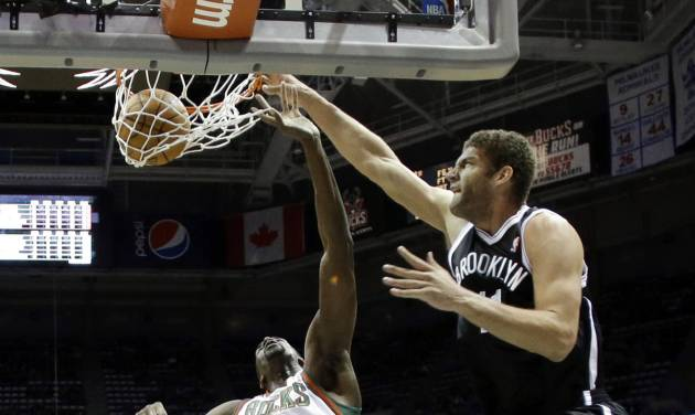 Brooklyn Nets' Brook Lopez dunks over Milwaukee Bucks' Ekpe Udoh (5) during the first half of an NBA basketball game Saturday, Dec. 7, 2013, in Milwaukee. (AP Photo/Morry Gash)