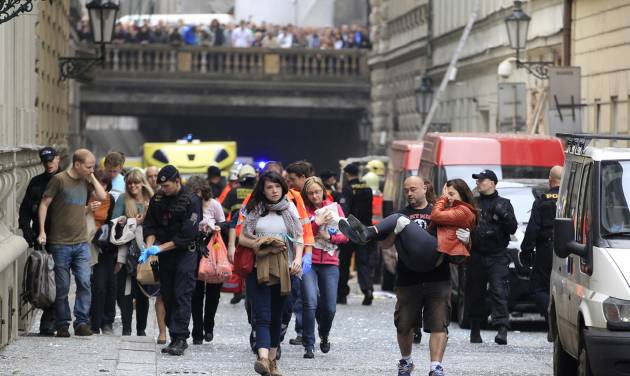 Injured people leave a scene of an explosion in downtown Prague, Czech Republic, Monday, April 29, 2013. Police said a powerful explosion has damaged a building in the center of the Czech capital and they believe some people are buried in the rubble. (AP Photo/Petr David Josek)