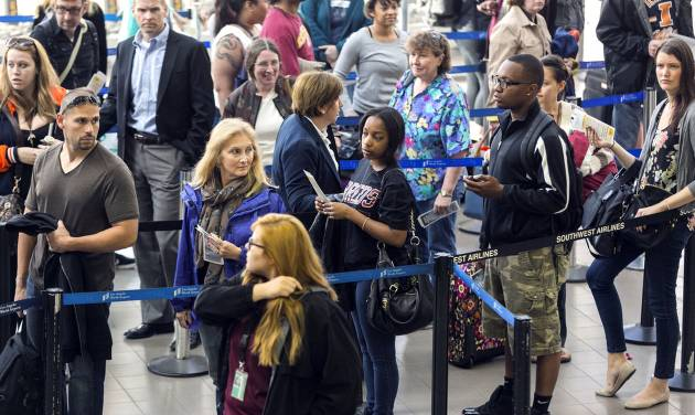 Travelers stand in line at Los Angeles International airport in Los Angeles Monday, April 22, 2013.  It was a tough start to the week for many air travelers. Flight delays piled up Monday as thousands of air traffic controllers were forced to take an unpaid day off because of federal budget cuts. (AP Photo/Damian Dovarganes)