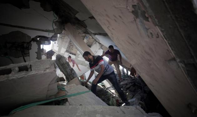 Palestinians search for survivors under the rubble of a house was destroyed by an Israeli missile strike, in Gaza City, Monday, July 21, 2014. On Sunday, the first major ground battle in two weeks of Israel-Hamas fighting exacted a steep price, killing scores of Palestinians and over a dozen Israeli soldiers and forcing thousands of terrified Palestinian civilians to flee their devastated Shijaiyah neighborhood, which Israel says is a major source for rocket fire against its civilians. (AP Photo/Khalil Hamra)