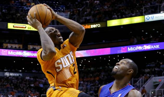 Phoenix Suns' Eric Bledsoe (2) goes in for a shot as Detroit Pistons' Rodney Stuckey defends during the second half of an NBA basketball game, Friday, March 21, 2014, in Phoenix. The Suns won 98-92. (AP Photo/Matt York)
