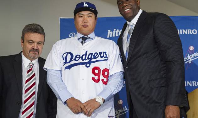 Los Angeles Dodgers general manager Ned Colletti, left, and co-owner Magic Johnson, right, present pitcher Ryu Hyun-jin, center, of South Korea, during a baseball news conference announcing his $36 million, six-year contract, Monday, Dec. 10, 2012, in Los Angeles. Ryu becomes the first player to go directly from the Korea Baseball Organization to the United States big leagues. (AP Photo/Damian Dovarganes)