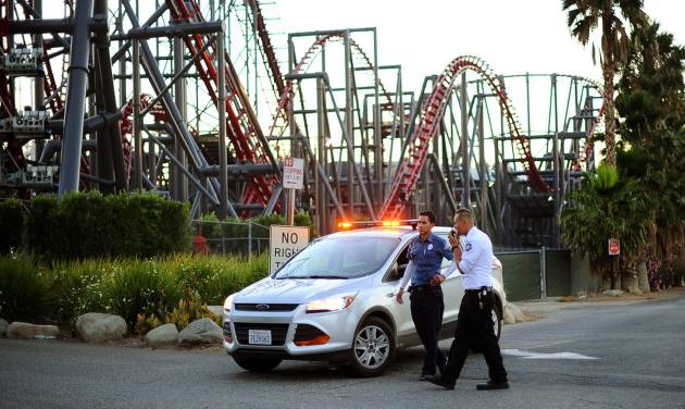 Members of the Six Flags Magic Mountain amusement park security staff monitor the situation at the exit of the park after riders were injured on the Ninja coaster Monday, July 7, 2014, in Valencia, Calif. The roller coaster hit a tree branch dislodging the front car, leaving four people slightly injured and keeping nearly two dozen summer fun-seekers hanging 20 to 30 feet in the air for hours as day turned to night. Two of the four people hurt on the Ninja coaster were taken to the hospital as a precaution, but all the injuries were minor, fire and park officials said. (AP Photo/Los Angeles Daily News, Andy Holzman)