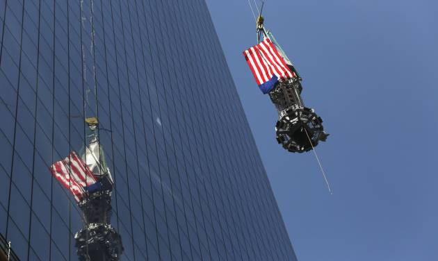 The final piece of the spire is hoisted to the roof of One World Trade Center in New York, Thursday, May 2, 2013. The piece will be attached to the spire at a later date, capping off the tower at 1,776 feet. (AP Photo/Mark Lennihan)