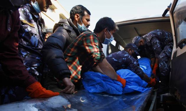 Hospital officials and Nepalese police officers carry the remains of a plane crash victim out from an ambulance upon arrival at a teaching hospital in Katmandu, Nepal, Monday, Feb. 17, 2014. Rescuers on Monday found the wreckage of the passenger plane that slammed into a snow-covered mountain and burst into flames, killing all 18 people on board, including a small child, authorities said. (AP Photo/Niranjan Shrestha)