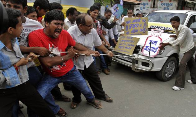 """Indian people pull a car by rope and shout slogans during a protest against the price hike in diesel and capping the number of subsidized cooking gas cylinders in Ahmadabad, India, Friday, Sept. 14, 2012. India's government is facing angry protests from its political allies as well as the opposition after it raised the price of diesel fuel in a bid to curb its ballooning fiscal deficit and also announced a reduction in cooking gas subsidies. The replica of cooking gas cylinder on the right reads as """"down with price rise."""" (AP Photo/Ajit Solanki)"""