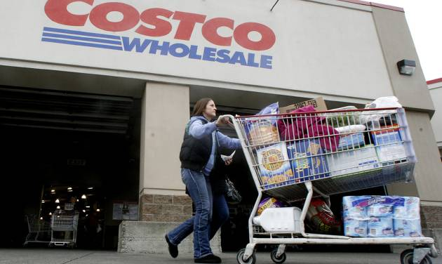 FILE- In this Wednesday, Dec. 7, 2011, file photo, a shopper leaves a Costco store in, Portland, Ore. Many companies are making special end-of-year dividend payments or moving up their quarterly payouts because investors will have to pay higher taxes on dividend income starting in 2013, unless Congress and President Barack Obama reach a compromise on taxes and government spending. (AP Photo/Rick Bowmer, File)