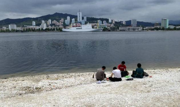 In this Sunday, June 22, 2014 photo taken with smartphone camera, North Koreans have a picnic in a beach with a ferry Mangyongbong-92 anchored, in the background in Wonsan, North Korea. Wonsan, a sleepy port on North Korea's east coast, is gearing up for a busy summer - and, if talks with Japan go as North Korea hopes, maybe a return to livelier days. (AP Photo/Eric Talmadge)