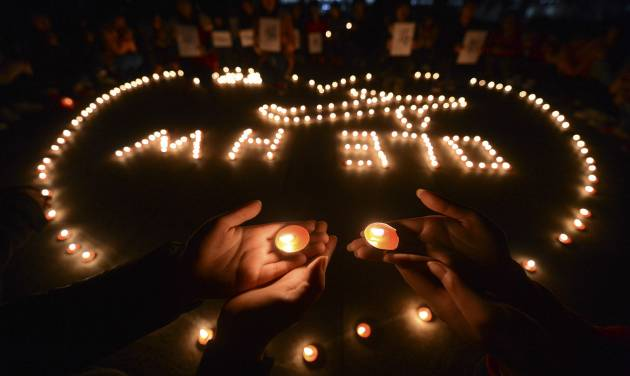 In this March 13, 2014 file photo, university students hold a candlelight vigil for passengers on the missing Malaysia Airlines Flight MH370 in Yangzhou, in eastern China's Jiangsu province. The disappearance of Malaysia Airlines Flight 370 has exposed wide gaps in how the world's airlines, and their regulators, operate. But experts warn this isn't likely to be one of those defining moments that lead to fundamental changes. (AP Photo/File)  CHINA OUT