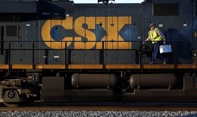 In this March 22, 2014 picture, a crew member walks on a CSX freight train engine in Brunswick, Md. CSX Corp. reports quarterly earnings after the market close on Tuesday, April 15, 2014. (AP Photo/Patrick Semansky)