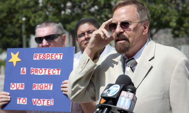 Thomas Coleman, right, with Robert Doriah, speaks at news conference Thursday July 10, 2014 in Los Angeles to propose full voting rights and access for the disabled. A Voting Rights Act complaint submitted Thursday to the U.S. Justice Department in Los Angeles goes to a politically delicate subject that states have grappled with over the years: Where is the line to disqualify someone from the voting booth because of a cognitive or developmental impairment?  (AP Photo/Nick Ut)