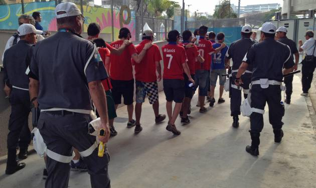 Detained fans of Chile's national soccer team, are marched away by security forces toward a holding area, after they broke through a stadium security checkpoint, in Rio de Janeiro, Brazil, Wednesday June 18, 2014. Nearly 100 rampaging Chilean fans busted through the checkpoint at the Maracana stadium Wednesday, sprinting through a large media room and breaking down walls trying to find a way into the sold-out Spain vs. Chile World Cup match. (AP Photo/Jorge Sainz)