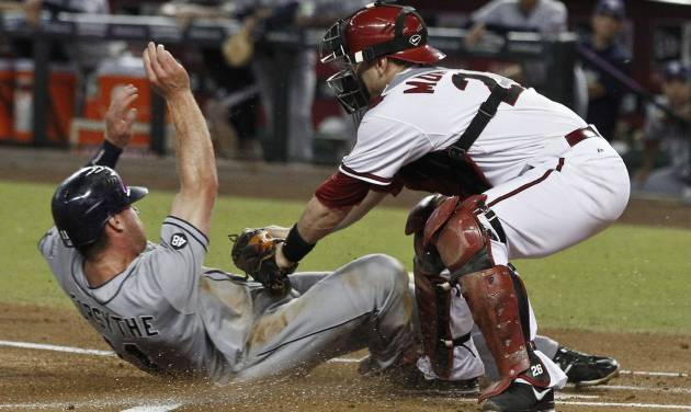 San Diego Padres' Logan Forsythe, left, scores a run as he slides under the tag of Arizona Diamondbacks' Miguel Montero during the first inning during a baseball game Tuesday, Sept. 18, 2012, in Phoenix. (AP Photo/Ross D. Franklin)