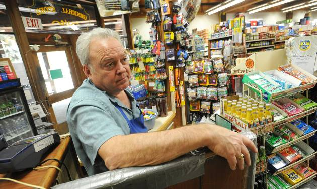 File - In this Aug. 24, 2013 file photo, Pinecrest General Store owner Dan Vaughn stands in his empty business in Pinecrest, Calif. Vaughn says that business is down 90% from normal at this time of year as a result of the Rim Fire which continues to burn in the Stanislaus National Forest.  Vaughn sent four of his employees home due to the lack of business. It doesn't pay to be a dateline in a disaster story, as the folks around Groveland, Calif. will tell you. On what would have been the busiest weekend of the summer had the Strawberry Music Festival not been cancelled, hotel rooms are empty and the local coffee roaster got rid of all 6 employees because the road to Yosemite is closed. One hotelier has had $20,000 in cancellations just this week. In the park, tourists are enjoying elbow room as hard-to-get campsite and lodging rooms are full but day tourists are staying away out of fear of fire and smoke. (AP Photo/The Modesto Bee, Elias Funez, File)