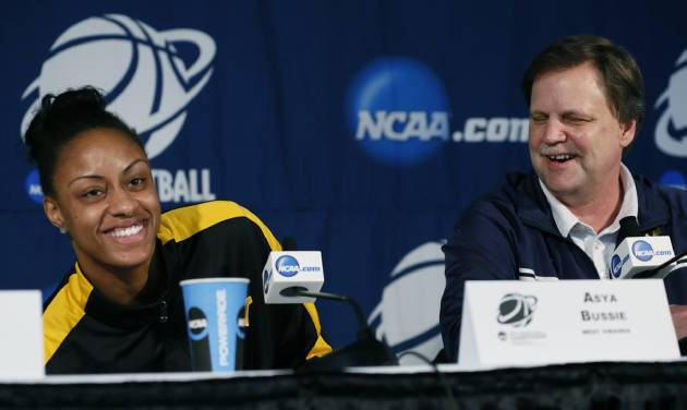 West Virginia basketball coach Mike Carey laughs at center Asya Bussie's reaction to her cell phone ringing during a news conference prior to practice at the NCAA women's college basketball tournament in Baton Rouge, La., Monday, March 24, 2014. West Virginia faces LSU in the second-round game on Tuesday. (AP Photo/Rogelio V. Solis)