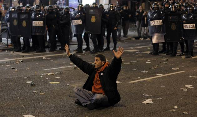 A protestor sits in front of the riot police riot to stop the clashes during a general strike in Madrid, Spain, Wednesday, Nov. 14, 2012. Spain's main trade unions stage a general strike, coinciding with similar work stoppages in Portugal and Greece, to protest government-imposed austerity measures and labor reforms. The strike is the second in Spain this year. (AP Photo/Andres Kudacki)