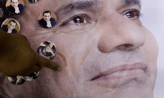 A man pins pictures of former Egyptian President Hosni on a poster showing presidential hopeful Abdel-Fattah el-Sissi, in Cairo, Egypt, Sunday, May 4, 2014. With only two people — former army chief Abdel-Fattah el-Sissi and leftist politician Hamdeen Sabahi — vying for the country's top post, the Egyptian election commission set the first round of voting for May 26 and 27, with results expected by June 5. (AP Photo/Amr Nabil)