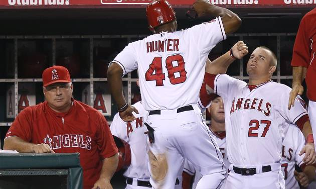 Los Angeles Angels' Torii Hunter, center, is greeted by teammate Mike Trout, right, after Hunter scored on a single by Howard Kendrick in the fourth inning of a baseball game against the Texas Rangers in Anaheim, Calif., Tuesday, Sept. 18, 2012. Los Angeles Angels manager Mike Scioscia, left, sits in the dugout. (AP Photo/Jae C. Hong)