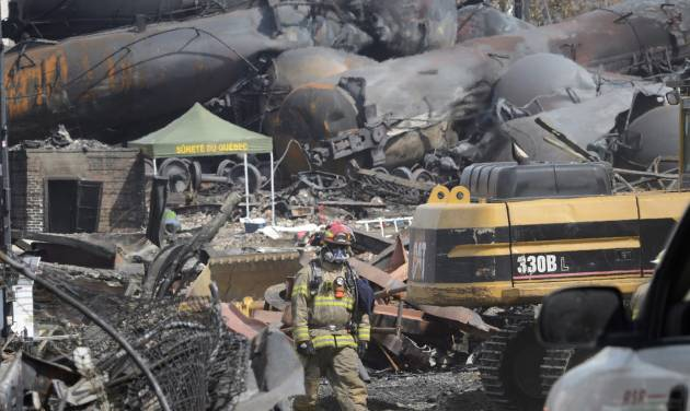 FILE - This July 6, 2013 file photo shows a worker, wearing protective gear moving though the wreckage of the oil train derailment and explosion in  in Lac-Megantic, Quebec. Responding to a series of fiery train derailments, federal regulators said Wednesday they will propose that trains transporting crude oil have at least two-man crews and requirements aimed at preventing parked train cars from coming loose and causing an accident like one in July that killed 47 people. The Federal Railroad Administration had asked a freight rail industry advisory committee to make recommendations on whether two-man crews should be required, but the industry officials were unable to reach a consensus after working on the issue for months. Federal officials said they decided to move ahead with the two-crew member requirement anyway.  (AP Photo/Ryan Remiorz, File, Pool)
