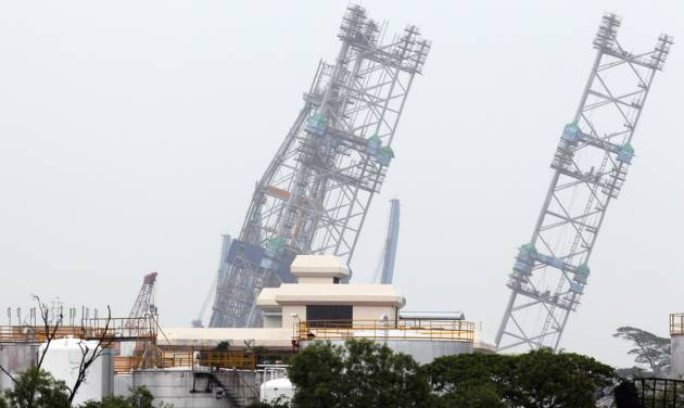 A backup rig is seen tilted to one side off a shipyard on Monday Dec. 3, 2012 in Singapore. The ministry of manpower reported that about 90 workers were sent to hospitals after a jackup rig at a shipyard in Singapore tilted to one side.(AP Photo/Wong Maye-E)