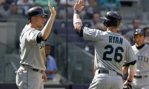 Seattle Mariners' Brendan Ryan, right, and Alex Liddi celebrate after scoring on a single by Casper Wells during the ninth inning of a baseball game against the New York Yankees at Yankee Stadium in New York, Sunday, May 13, 2012. The Mariners defeated the Yankees 6-2. (AP Photo/Seth Wenig)
