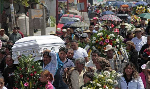 Men carry a coffin during a funeral procession in the town of Jesus Tepactepec, Mexico, Sunday, March 17, 2013. A mass funeral was held for 13 of the 16 victims of a gruesome fireworks explosion during a religious procession on Friday. A total of about 154 were injured when a rocket malfunctioned and landed on the truck, igniting the fireworks it carried. (AP Photo/J. Guadalupe Perez)