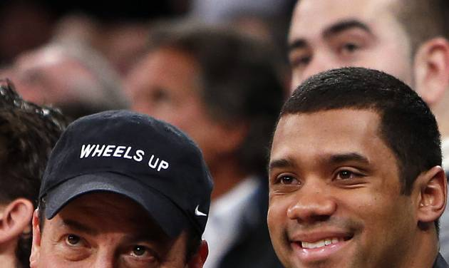 Kenny Dichter, CEO of Wheels Up, left, and Seattle Seahawks quarterback Russell Wilson pose for a photograph together as they attend an NBA basketball game between the Dallas Mavericks and the New York Knicks, Monday, Feb. 24, 2014, in New York. Dallas won 110-108. (AP Photo/Jason DeCrow)