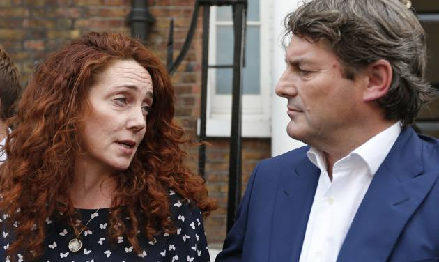 Rebekah Brooks, left, former News International chief executive, looks at her husband Charlie, right, as she talks to members of the media in central London, Thursday, June 26, 2014. Brooks was acquitted after a long trial centering on illegal activity at the heart of Rupert Murdoch's newspaper empire but Former News of the World editor Andy Coulson was convicted of phone hacking. The nearly eight-month trial was triggered by revelations that for years the News of the World used illegal eavesdropping to get stories, listening in on the voicemails of celebrities, politicians and even crime victims. (AP Photo/Lefteris Pitarakis)