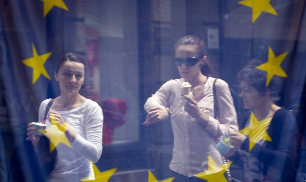 A street scene is reflected in the window of a library with an EU flag on display  in downtown  Zagreb, Croatia, Sunday, June 30, 2013. Croatia is to join the European Union on July 1, 2013. (AP Photo/Darko Bandic)
