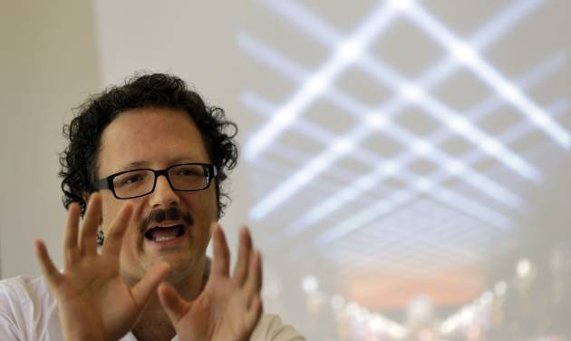 """In this Aug. 23, 2012 photo, artist Rafael Lozano-Hemmer discusses his new project titled """"Open Air,"""" commissioned by the Association for Public Art, in Philadelphia. The interactive light installation using 24 robotic searchlights plans to illuminate the night sky over the Benjamin Franklin Parkway from the scheduled dates of Sept. 20 to Oct 14. (AP Photo/Matt Rourke)"""