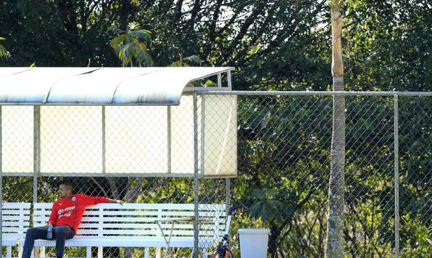 Chile's Arturo Vidal sits on a bench during a training session at Toca da Raposa 2, in Belo Horizonte, Brazil, Monday, June 9, 2014. Vidal, who is recovering from an injury, did not train. Chile will play in group B of the Brazil 2014 World Cup. (AP Photo/Bruno Magalhaes)