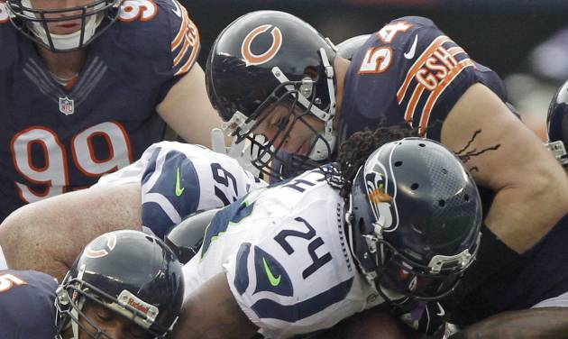 Seattle Seahawks running back Marshawn Lynch (24) is tackled by Chicago Bears safety Craig Steltz (20) and linebacker Brian Urlacher (54) in the first half of an NFL football game in Chicago, Sunday, Dec. 2, 2012. (AP Photo/Kiichiro Sato)