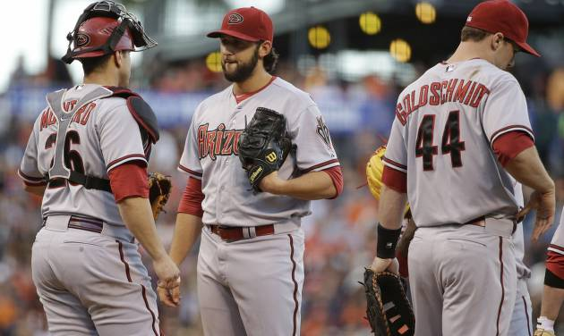 Arizona Diamondbacks starting pitcher Mike Bolsinger, center, talks with catcher Miguel Montero, left, after the San Francisco Giants scored their third run in the second inning of their baseball game on Friday, July 11, 2014, in San Francisco. First baseman Paul Goldschmidt, right, looks on.  San Francisco won the game 5-0. (AP Photo/Eric Risberg)