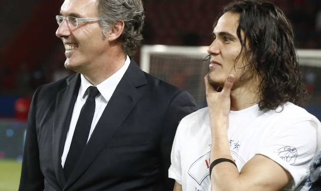 Paris Saint-Germain's coach Laurent Blanc, left, and Uruguayan Edinson Cavani, right, stand together after the French league one soccer match between Paris-Saint-Germain and Rennes at Parc des Princes stadium in Paris, Wednesday, May 7, 2014. Paris Saint- Germain clinched their second straight French league title on Wednesday after rival Monaco drew 1-1 against French Cup holder Guingamp. (AP Photo/Michel Euler)