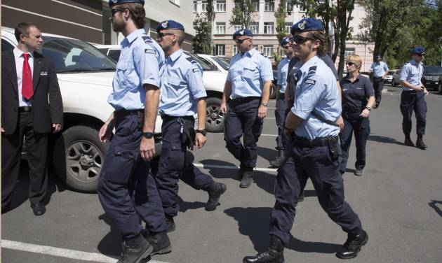 Dutch policemen walk in the city of Donetsk, eastern Ukraine Sunday, July 27, 2014. A team of international police officers that had been due to visit the site of the Malaysian plane disaster in eastern Ukraine cancelled the trip Sunday after receiving reports of fighting in the area. Alexander Hug, the deputy head of a monitoring team from the OSCE in Europe, said it would be too dangerous for the unarmed mission to travel to the site from its current location in the rebel-held city of Donetsk. (AP Photo/Dmitry Lovetsky)