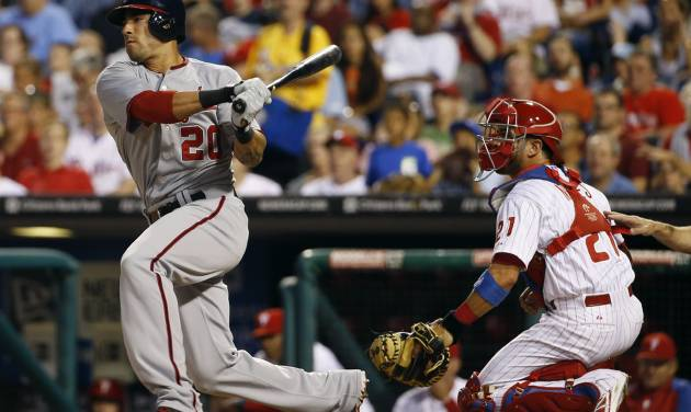 Washington Nationals' Ian Desmond, left, follows through after follows through after hitting an RBI-single off Philadelphia Phillies starting pitcher Kyle Kendrick during the first inning of a baseball game, Wednesday, Aug. 27, 2014, in Philadelphia. At right is catcher Wil Nieves. (AP Photo/Matt Slocum)