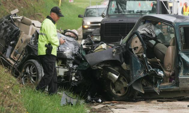 FILE - In this April 19, 2009 file photo, North Carolina Highway Patrolman R. Grayson investigates a two-vehicle wreck on U.S. 64 near Brevard, N.C., that killed three people, including a child, in the head-on collision. A freak accident on New York's Bronx River Parkway that wiped out three generations of a family on April 29, 2012, is being touted by some transportation advocates as more evidence that New York City's aging highway system needs major upgrades. Yet, while New York City saw 243 people killed in traffic accidents in 2011, by comparison, North Carolina, a state with a population not much larger than New York City, had 1,314 motor vehicle fatalities in 2009. (AP Photo/Times-News, Mike Dirks, File)