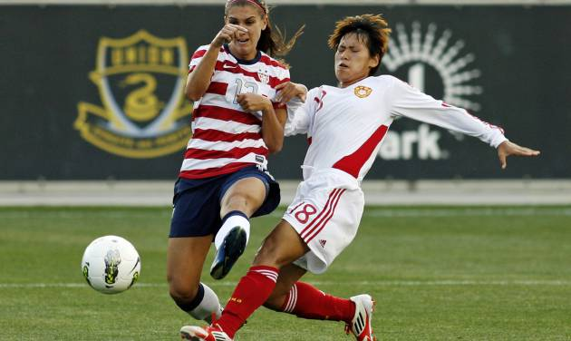 United States' Alex Morgan (13) takes a shot as China's Han Peng (18) defends during the first half of their international friendly soccer match in Chester, Pa., Sunday, May 27, 2012. (AP Photo/H. Rumph Jr.)