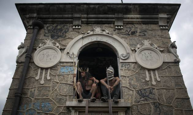 A man wearing a headdress and another wearing a ski mask sit on a windowsill on the site of an old Indian museum, now abandoned, in Rio de Janeiro, Brazil, Saturday, Jan. 12, 2013. Police in riot gear on Saturday surrounded the abandoned museum, now an indigenous settlement of men and women living in 10 homes, preparing to enforce their eviction. Their settlement is next to the Maracana stadium, which is being refurbished to host the opening and closing ceremonies of the 2016 Olympics and the final match of the 2014 World Cup. The streets around the stadium will also undergo a vast transformation as part of the area's transformation into a shopping and sports entertainment hub. (AP Photo/Felipe Dana)