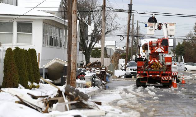 Utility workers check the power lines as snow covered debris from Superstorm Sandy lay on the side of a street following a nor'easter storm, Thursday, Nov. 8, 2012, in Point Pleasant, N.J. The New York-New Jersey region woke up to wet snow and more power outages Thursday after the nor'easter pushed back efforts to recover from Superstorm Sandy, that left millions powerless and dozens dead last week. (AP Photo/Julio Cortez)