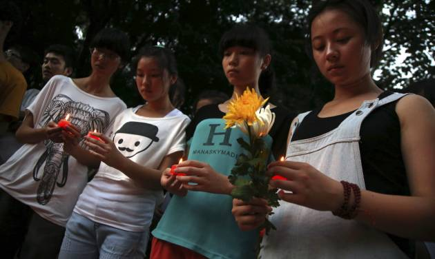Residents gather to mourn for the two victims of the Asiana airline plane crash in San Francisco at a park in Jiangshan city in eastern China's Zhejiang province on Monday, July 8 2013. Chinese state media and Asiana Airlines have identified the two victims of the Asiana Airlines crash at San Francisco International Airport girls as Ye Mengyuan and Wang Linjia, students in Zhejiang, an affluent coastal province in eastern China.  (AP Photo) CHINA OUT