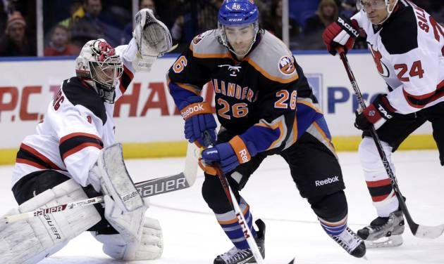 New York Islanders' Matt Moulson, center, maneuvers the puck between the New Jersey Devils goalie Johan Hedberg, left, and Bryce Salvador during the second period of the NHL hockey game on Sunday, Feb. 3, 2013, in Uniondale, N.Y. (AP Photo/Seth Wenig)