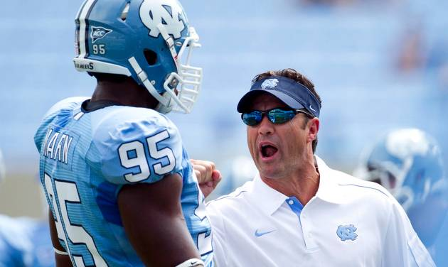 North Carolina head coach Larry Fedora has a word with Kareem Martin (95) during the Tar Heels' pre-game warm up for their season-opening NCAA college football game against Elon, Saturday Sept. 1, 2012, at Kenan Stadium in Chapel Hill, N.C. (AP Photo/The News & Observer, Robert Willett) MANDATORY CREDIT