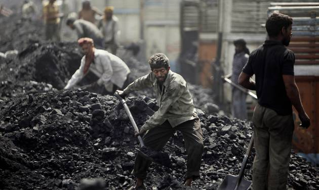 FILE- In this Friday, March 23, 2012, file photo, Indian laborers load coal onto trucks at a coal depot on the outskirts of Jammu, India. India's national auditor said Friday, Aug. 17, 2012, the government lost huge sums of money by selling coal fields to private companies without competitive bidding, adding to massive losses from dubious auctions of other state assets. The Comptroller and Auditor General's report to Parliament estimated that private companies got a windfall profit of $34 billion because of the low prices they paid for the fields. (AP Photo/Channi Anand, File)