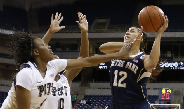 Notre Dame's Taya Reimer (12) shoots over Pittsburgh's Loliya Briggs (1) and another defender during the first half of an NCAA college basketball game Thursday, Jan. 16, 2014, in Pittsburgh. (AP Photo/Keith Srakocic)