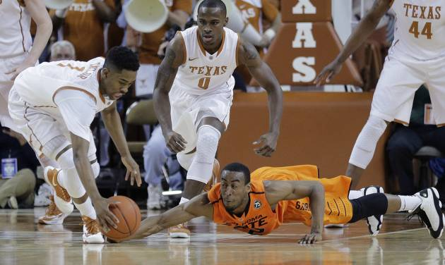 Texas' Isaiah Taylor (1) and Oklahoma State's Markel Brown (22), scramble for a loose ball during the first half on an NCAA college basketball game, Tuesday,  Feb. 11, 2014, in Austin, Texas. (AP Photo/Eric Gay)