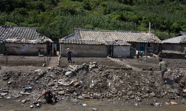 In this Monday, Aug 13, 2012 photo, North Koreans sift through their belongings near their homes, damaged by July 2012 flooding, in Ungok, North Korea. Twin typhoons are renewing fears of a humanitarian crisis in North Korea, where poor drainage, widespread deforestation and fragile infrastructure can turn even a routine rainstorm into a catastrophic flood. (AP Photo/David Guttenfelder)